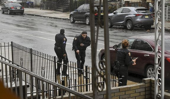 In this Dec. 10, 2019, photo, Jersey City police Sgt. Marjorie Jordan, left, helps fellow officer Raymond Sanchez to safety after he was shot during a gunfight that left multiple dead in Jersey City, N.J. The two killers were armed with a variety of weapons, including an AR-15-style rifle and a shotgun that they were wielding when they stormed into a store in an attack that left the scene littered with several hundred shell casings, broken glass and a community in mourning. Despite years of New Jersey officials focusing on the problems of crime guns coming into the state, Tuesday's shooting shows efforts are falling short. (Justin Moreau via AP)