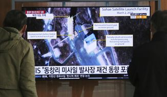 """FILE - In this March 6, 2019, file photo, people watch a TV screen showing an image of the Sohae Satellite Launching Station in Tongchang-ri, North Korea, during a news program at the Seoul Railway Station in Seoul, South Korea. North Korea on Saturday, Dec. 14, says it successfully performed another """"crucial test"""" as its long-range rocket launch site that would further strengthen its """"reliable strategic nuclear deterrent.""""The signs read: """" North's Tongchang-ri launch site."""" (AP Photo/Ahn Young-joon, File)"""