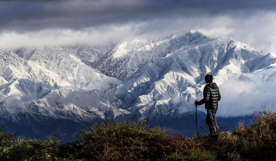In this Nov. 29, 2019 file photo Frank Huong takes a break from hiking to enjoy a view of snow-capped San Gabriel Mountains from Hidden Hills trail in Chino Hills, Calif. (Watchara Phomicinda/The Orange County Register via AP, File) ** FILE **
