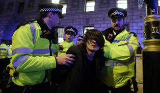 Police take away a protester during an anti-Boris Johnson demonstration, at Trafalgar Square in central London, Friday Dec. 13, 2019. Boris Johnson's gamble on early elections paid off as voters gave the UK prime minister a commanding majority to take the country out of the European Union by the end of January, a decisive result after more than three years of stalemate over Brexit. (AP Photo/Kirsty Wigglesworth)