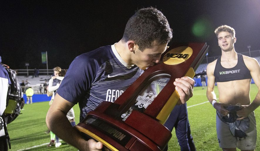Georgetown's Jack Beer (11) kisses the trophy after defeating Virginia in the NCAA college soccer championship in Cary, N.C., Sunday, Dec. 15, 2019. (AP Photo/Ben McKeown)  **FILE**