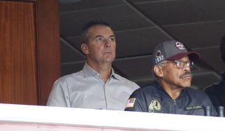 Three-time national champion college football coach Urban Meyer, center, watches Philadelphia Eagles and Washington Redskins NFL football game during the first half from Dan Snyder's box at FedEx Field, Sunday, Dec. 15, 2019, in Landover, Md. (AP Photo/Patrick Semansky)