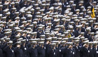 Navy midshipmen salute ahead of an NCAA college football game against Army, Saturday, Dec. 14, 2019, in Philadelphia. (AP Photo/Matt Slocum)
