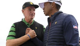 International team captain Ernie Els, left, shakes hands with U.S. team player and captain Tiger Woods after the U.S. team won the President's Cup golf tournament at Royal Melbourne Golf Club in Melbourne, Sunday, Dec. 15, 2019. The U.S. team won the tournament 16-14. (AP Photo/Andy Brownbill)