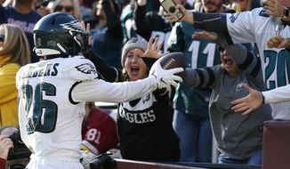 Philadelphia Eagles running back Miles Sanders (26) hands the ball to fans after scoring a touchdown against the Washington Redskins in the first half of an NFL football game, Sunday, Dec. 15, 2019, in Landover, Md. (AP Photo/Alex Brandon)