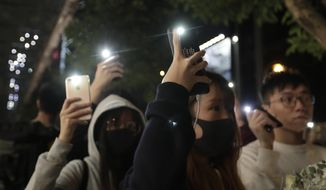 Attendees hold up their lit mobile phones to mark the six months anniversary memorial for a man who fell to his death while hanging a protest banner against an extradition bill, in Hong Kong Sunday, Dec. 15, 2019 in Hong Kong. (AP Photo/Mark Schiefelbein)