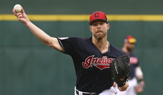 FILE - In this March 11, 2019, file photo, Cleveland Indians starting pitcher Corey Kluber throws a warm up pitch before a spring training baseball game against the Cincinnati Reds in Goodyear, Ariz. The Indians are close to completing a trade that will send the two-time Cy Young Award winner Corey Kluber to the Texas Rangers, a person familiar with the negotiations told The Associated Press on Sunday, Dec. 15, 2019. (AP Photo/Ross D. Franklin, File)
