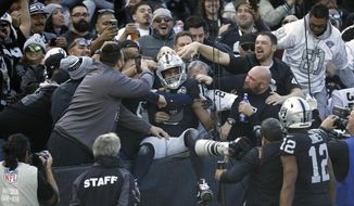 Oakland Raiders wide receiver Tyrell Williams is mobbed by fans after scoring a touchdown during the first half of an NFL football game against the Jacksonville Jaguars in Oakland, Calif., Sunday, Dec. 15, 2019. (AP Photo/Ben Margot)