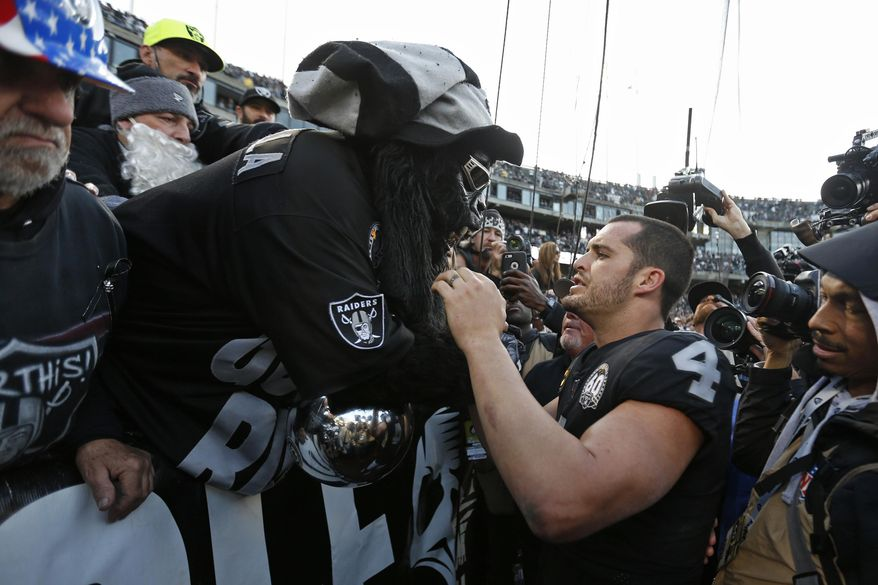"""Oakland Raiders quarterback Derek Carr (4) is met by Gorilla Nilla in """"The Black Hole"""" at the end of an NFL football game against the Jacksonville Jaguars in Oakland, Calif., Sunday, Dec. 15, 2019. (AP Photo/D. Ross Cameron)"""