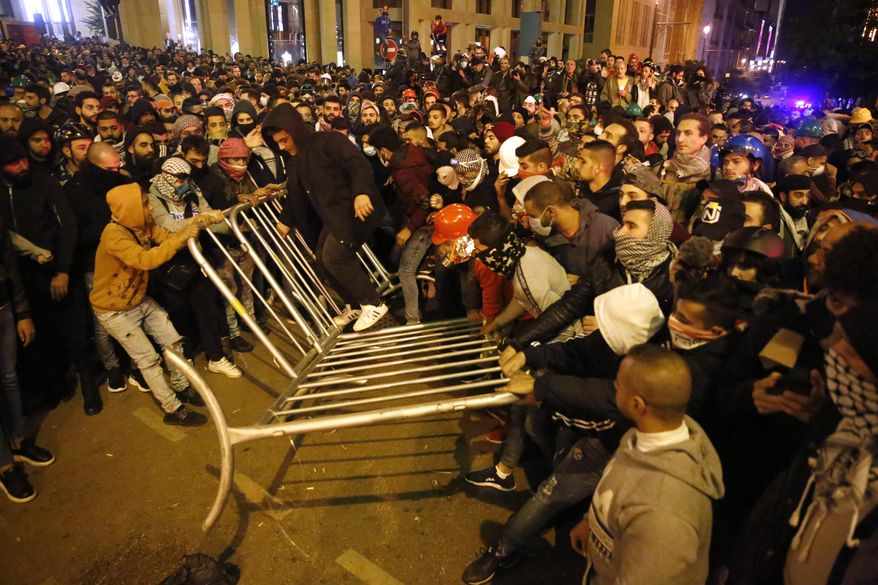 Anti-government protesters remove the fences that was divided between them and the riot police, during a protest near the parliament square, in downtown Beirut, Lebanon, Sunday, Dec. 15, 2019. Lebanese security forces fired tear gas, rubber bullets and water cannons Sunday to disperse hundreds of protesters for a second straight day, ending what started as a peaceful rally in defiance of the toughest crackdown on anti-government demonstrations in two months. (AP Photo/Hussein Malla)