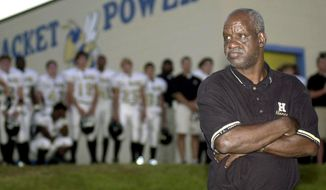 "FILE - In this Sept. 19, 2003 file photo James ""Radio"" Kennedy stands with the T.L. Hanna High School varsity football team behind him just before Friday night's game against Fort Mill in Fort Mill, S.C. Kennedy, the man who was a fixture on the sidelines of the South Carolina high school's football games for decades and whose life inspired a Hollywood movie, died Sunday, Dec. 15, 2019. He was 73. (Amber M. McCloskey/The Herald via AP, File)"