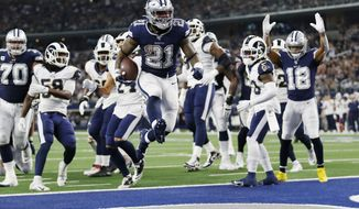 Dallas Cowboys running back Ezekiel Elliott (21) jumps into the end zone with a touchdown in front of Los Angeles Rams defensive back Darious Williams (31) in the first half an NFL football game in Arlington, Texas, Sunday, Dec. 15, 2019. (AP Photo/Roger Steinman)