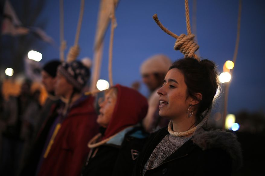 Activists protest outside of the COP25 climate talks congress in Madrid, Spain, Saturday, Dec. 14, 2019. The United Nations Secretary-General has warned that failure to tackle global warming could result in economic disaster. (AP Photo/Manu Fernandez)