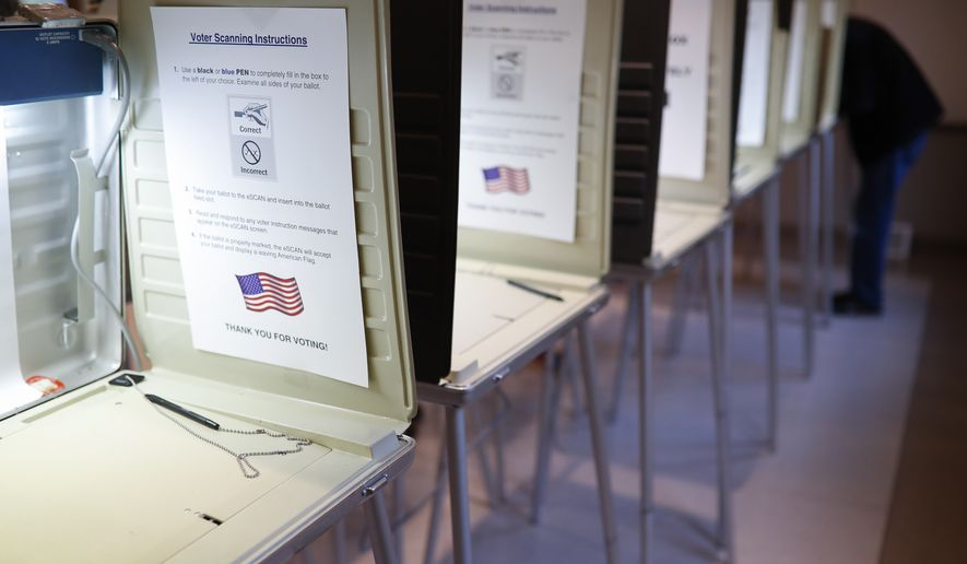 In this Nov. 8, 2016, file photo a lone voter fills out a ballot alongside a row of empty booths at a polling station in the Terrace Park Community Building on Election Day in Cincinnati, Ohio. A federal judge on Friday, Dec.27, refused to intercede to stop the state of Georgia from cleaning up its voter registration list to remove around 120,000 inactive voters. (AP Photo/John Minchillo, File) **FILE**