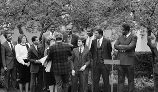 U.S.President Ronald Reagan shakes hands with Patrick Ewing, left, and Michael Graham, right, as Georgetown University academic coordinator Mary Fenlon looks on, during a ceremony for the Georgetown University NCAA Champion basketball team, in the Rose Garden of the White House, Saturday, April 7, 1984 in Washington. (AP Photo/Charles Tasnadi) **FILE**