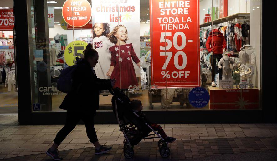 A shopper walks in front of Christmas sales signs Monday, Dec. 16, 2019, in Santa Clarita, Calif. (AP Photo/Marcio Jose Sanchez) **FILE**