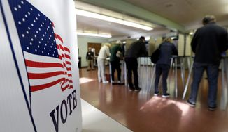 In this Nov. 6, 2018, file photo, voters cast their ballots, in Gates Mills, Ohio. An Associated Press review has found that thousands of Ohio voters were held up or stymied in their efforts to get absentee ballots by mail in 2018's general election because of a missing or mismatched signature on their ballot application. (AP Photo/Tony Dejak, File)  **FILE**