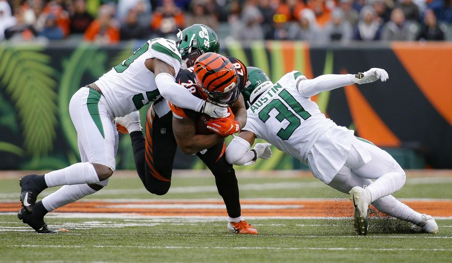 Cincinnati Bengals running back Joe Mixon (28) runs the ball against New York Jets outside linebacker James Burgess, left, and defensive back Blessuan Austin (31) during the first half of an NFL football game, Sunday, Dec. 1, 2019, in Cincinnati. (AP Photo/Frank Victores)