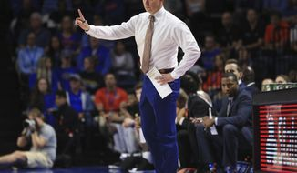 Florida coach Mike White motions to his team during the first half of an NCAA college basketball game against Marshall on Friday, Nov. 29, 2019, in Gainesville, Fla. (AP Photo/Matt Stamey)