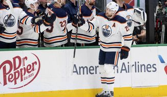 Edmonton Oilers center Leon Draisaitl (29) is congratulated by teammates on the bench after scoring a goal against the Dallas Stars in the first period of an NHL hockey game, Monday, Dec. 16, 2019, in Dallas. (AP Photo/Jeffrey McWhorter)