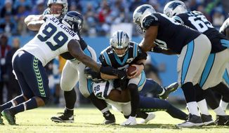 Seattle Seahawks defensive tackle Quinton Jefferson (99) and defensive end Rasheem Green (98) sack Carolina Panthers quarterback Kyle Allen (7) during the first half of an NFL football game in Charlotte, N.C., Sunday, Dec. 15, 2019. (AP Photo/Brian Blanco)
