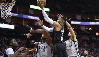Houston Rockets guard Russell Westbrook (0) drives to the basket as as San Antonio Spurs center LaMarcus Aldridge (12) and guard Derrick White, right, defend during the first half of an NBA basketball game, Monday, Dec. 16, 2019, in Houston. (AP Photo/Eric Christian Smith)