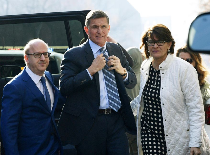 In this file photo, Michael Flynn, center, arrives at federal court in Washington. A judge set a sentencing hearing for Michael Flynn after rejecting arguments from the former Trump administration national security adviser that prosecutors had withheld evidence favorable to his case.  (AP Photo/Susan Walsh, File) **FILE**