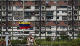 A woman watches the celebration rally of the 20th anniversary of the Venezuelan Constitution in Caracas, Venezuela, Sunday, Dec. 15, 2019. (AP Photo/Matias Delacroix)