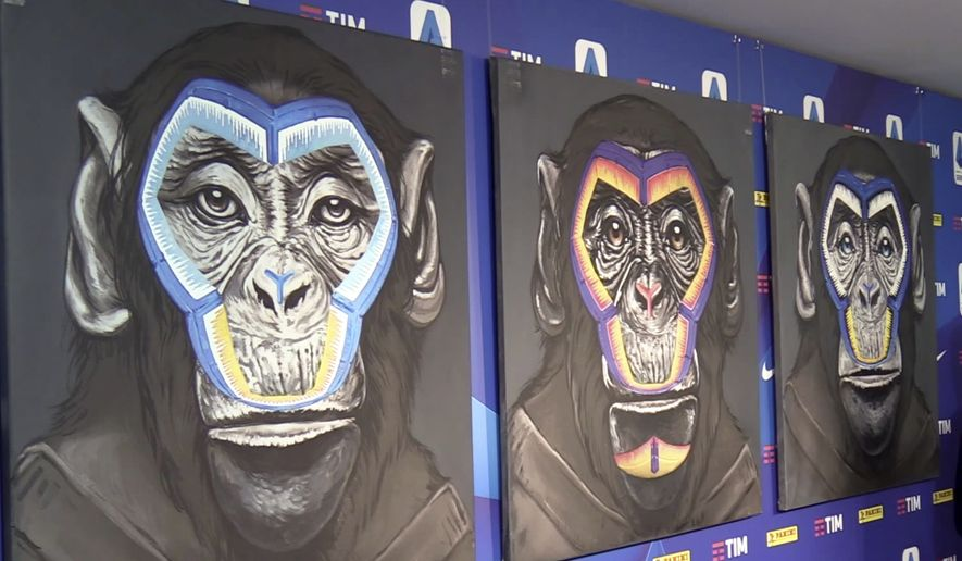 """A view of the three paintings, part of a new campaign against racism launched by the Italian soccer league in Milan, Italy, Monday, Dec. 16, 2019. While black players are regularly subjected to monkey chants in games, artist Simone Fugazzotto said his painting featuring three monkeys to represent three different races was meant to show that we are all the same race."""" The league used the painting at a presentation of its anti-racism campaign in Milan on Monday, stirring up controversy and criticism from both clubs and press. (ANSA via AP)"""