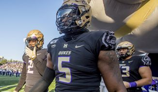 FILE - In this Nov. 16, 2019, file photo, James Madison defensive lineman Ron'Dell Carter (5) enters the field before the start of an NCAA football game, in Harrisonburg, Va. Carter was selected to The Associated Press FCS All-America first team, Tuesday, Dec. 17, 2019.  (Daniel Lin/Daily News-Record via AP)