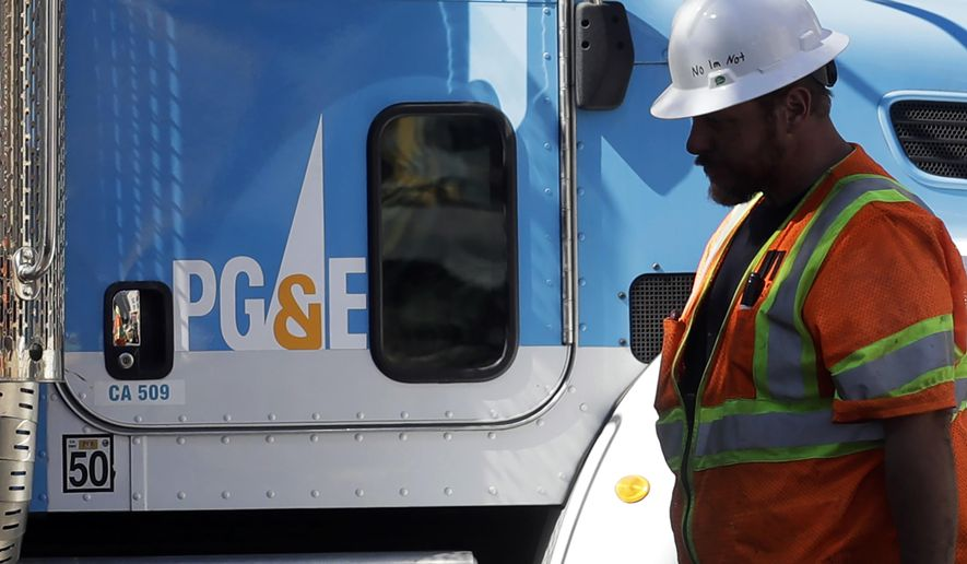 In this Aug. 15, 2019, file photo, a Pacific Gas & Electric worker walks in front of a truck in San Francisco. (AP Photo/Jeff Chiu, File)