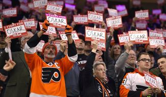Fans hold signs in support of Philadelphia Flyers' Oskar Lindblom during a stoppage in the first period of an NHL hockey game against the Anaheim Ducks, Tuesday, Dec. 17, 2019, in Philadelphia. (AP Photo/Derik Hamilton)