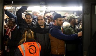 Commuters board in a subway, in Paris, Monday, Dec. 16, 2019. French President Emmanuel Macron suggested Thursday that he was ready to make changes to his plans to overhaul the pension system as a major union warned that nationwide strikes and protests could continue unabated until Christmas. (AP Photo/Thibault Camus)