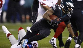 Philadelphia Eagles' Miles Sanders (26) is tackled by New York Giants' Janoris Jenkins (20) during the first half of an NFL football game, Monday, Dec. 9, 2019, in Philadelphia. (AP Photo/Matt Rourke)