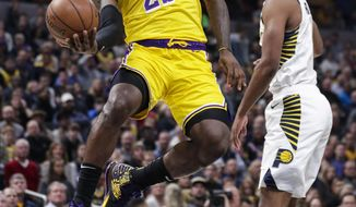 Los Angeles Lakers forward LeBron James (23) shoots behind Indiana Pacers forward T.J. Warren (1) during the first half of an NBA basketball game in Indianapolis, Tuesday, Dec. 17, 2019. (AP Photo/Michael Conroy)