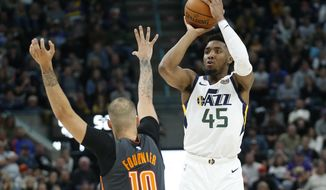 Utah Jazz guard Donovan Mitchell (45) shoots as Orlando Magic guard Evan Fournier (10) defends in the second half of an NBA basketball game Tuesday, Dec. 17, 2019, in Salt Lake City. (AP Photo/Rick Bowmer)