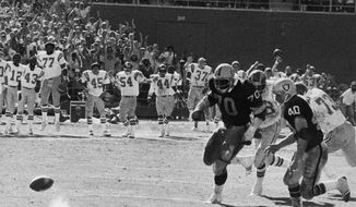 FILE - In this Sept. 11, 1978, file photo, Oakland Raiders Henry Lawrence (70) and Pete Banaszak (40) chase the bouncing ball during a football game against the San Diego Chargers, in San Diego. The stage was set in San Diego on Sept. 10, 1978, when the Raiders had the ball at the Chargers 14, trailing 20-14 with 10 seconds left. Ken Stabler dropped back to pass and was pressured by Chargers linebacker Woodrow Lowe. With nowhere to throw the ball, Stabler either fumbled or pushed the ball forward on purpose, depending on which side of the rivalry is telling the story. Teammate Pete Banaszak then knocked the ball further ahead from about the 13-yard line as it rolled toward the end zone. Tight end Dave Casper kicked the ball forward at the 5 and then fell on it in the end zone with no time remaining. (Thane McIntosh/The San Diego Union-Tribune via AP, File)