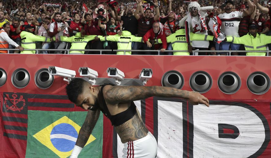 Flamengo's Gabriel Barbosa celebrates with Flamengo fans end of the Club World Cup semifinal soccer match between Flamengo and Al Hilal at the Khalifa International Stadium in Doha, Qatar, Tuesday, Dec. 17, 2019. (AP Photo/Hassan Ammar).