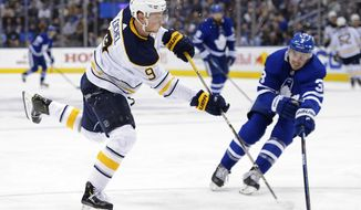 Buffalo Sabres centre Jack Eichel (9) shoots and scores as Toronto Maple Leafs defenseman Justin Holl (3) defends during third period NHL hockey action in Toronto on Tuesday, Dec. 17, 2019. (Nathan Denette/The Canadian Press via AP)