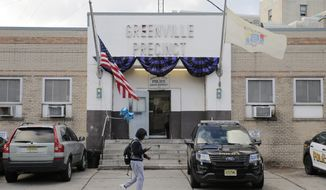 """Bunting hangs on the Greenville precinct in Jersey City, N.J., Wednesday, Dec. 11, 2019. The two gunmen in a furious firefight that left multiple people dead in Jersey City clearly targeted a Jewish market, the mayor said Wednesday, amid growing suspicions the bloodshed was an anti-Semitic attack. The shooting began near a cemetery, where Detective Joseph Seals, a 40-year-old member of a unit devoted to taking illegal guns off the street, was killed while trying to stop """"bad guys,"""" Police Chief Michael Kelly said without elaborating. (AP Photo/Seth Wenig)"""