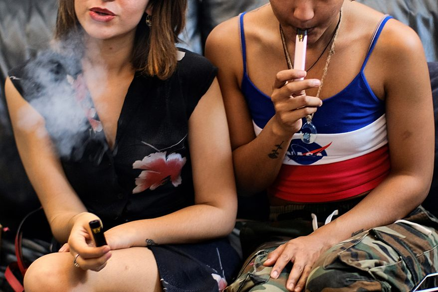 In this Saturday, June 8, 2019, file photo, two women smoke cannabis vape pens at a party in Los Angeles. On Thursday, Dec. 12, 2019, U.S. health officials said 26 states have reported deaths, for a total of 52. (AP Photo/Richard Vogel, File) ** FILE **
