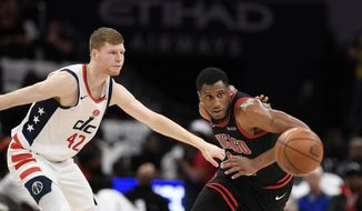 Washington Wizards forward Davis Bertans, left, and Chicago Bulls forward Thaddeus Young (21) watch the ball after Bertans lost possession of it during the first half of an NBA basketball game Wednesday, Dec. 18, 2019, in Washington. (AP Photo/Nick Wass)