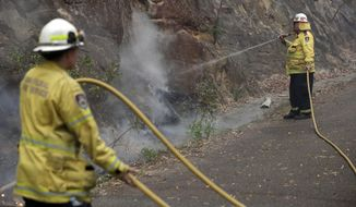 Firefighters keep an eye on the slow-moving fire near Mangrove Mountain, north of Sydney, Tuesday, Dec. 10, 2019. Hot dry conditions have brought an early start to the fire season. (AP Photo/Rick Rycroft)