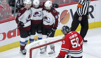 Colorado Avalanche's Andre Burakovsky, center, celebrates with Tyson Jost (17) and Nazem Kadri (91) Burakovosky's goal as Chicago Blackhawks goaltender Corey Crawford removes the puck from the net during the second period of an NHL hockey game Wednesday, Dec. 18, 2019, in Chicago. (AP Photo/Charles Rex Arbogast)