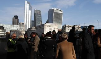 In this file photo dated Wednesday, Dec. 11, 2019, people gather near London Bridge, backdropped by the city of London financial district, with 20 Fenchurch Street building known as The Walkie-Talkie building, top right.  Prime Minister Boris Johnson's decisive victory in last week's general election provided little comfort to Britain's once world-beating financial services industry, which has been battered by Brexit for more than three years. (AP Photo/Thanassis Stavrakis, FILE)