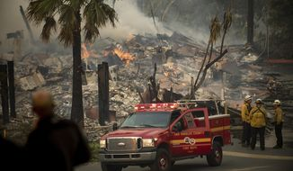 FILE - In this Dec. 5, 2017, file photo, an apartment complex burns as a wildfire rages in Ventura, Calif. More than a million California homes are now protected under a new law that temporarily bans insurance companies from dropping customers in areas affected by recent wildfires, officials announced Wednesday, Dec. 18, 2019. (AP Photo/Noah Berger, File)