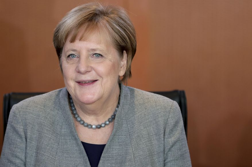 German Chancellor Angela Merkel smiles as she arrives for the weekly cabinet meeting at the Chancellery in Berlin, Germany, Wednesday, Dec. 18, 2019. (AP Photo/Michael Sohn)