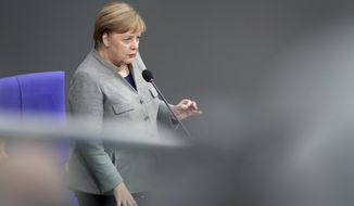 German Chancellor Angela Merkel takes questions as part of a meeting of the German parliament, Bundestag, at the Reichstag building in Berlin, Germany, Wednesday, Dec. 18, 2019. (AP Photo/Michael Sohn)