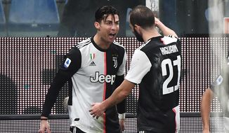 Juventus' Cristiano Ronaldo, left, celebrates with his teammate Gonzalo Higuain after scoring his side's second goal during a Serie A soccer match between Sampdoria and Juventus, at Luigi Ferraris stadium in Genoa, Italy, Wednesday, Dec. 18, 2019. (Luca Zennaro/ANSA via AP)