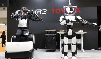 In this Dec. 18, 2019, photo, Toyota Motor Corp.'s human-shaped T-HR3 robot, right, is remotely controlled by its staff member, left, during a demonstration in Tokyo. Toyota's upgraded version of the human-shaped T-HR3 now has faster and smoother finger movements because the wearable remote-control device has become lighter and easier to use. The person wearing a headset and wiring made the robot move in exactly the same way he was moving, waving or making dance-like movements, as sensors sent computerized signals to the robot of what they detected as human movements. (AP Photo/Yuri Kageyama)